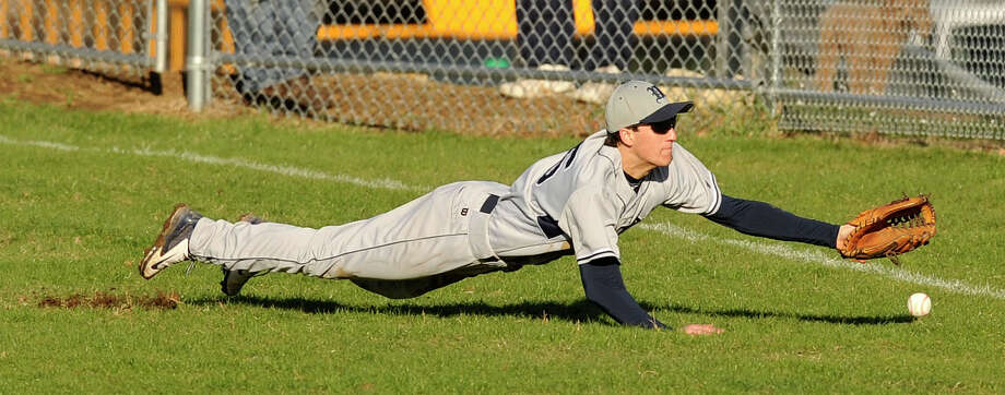 Wilton right fielder Paul Sorbo misses a diving catch during the Warriors' baseball game against Westhill at Westhill High School in Stamford, Conn., on Wednesday, April 16, 2014. Westhill won, 9-0. Photo: Jason Rearick / Stamford Advocate