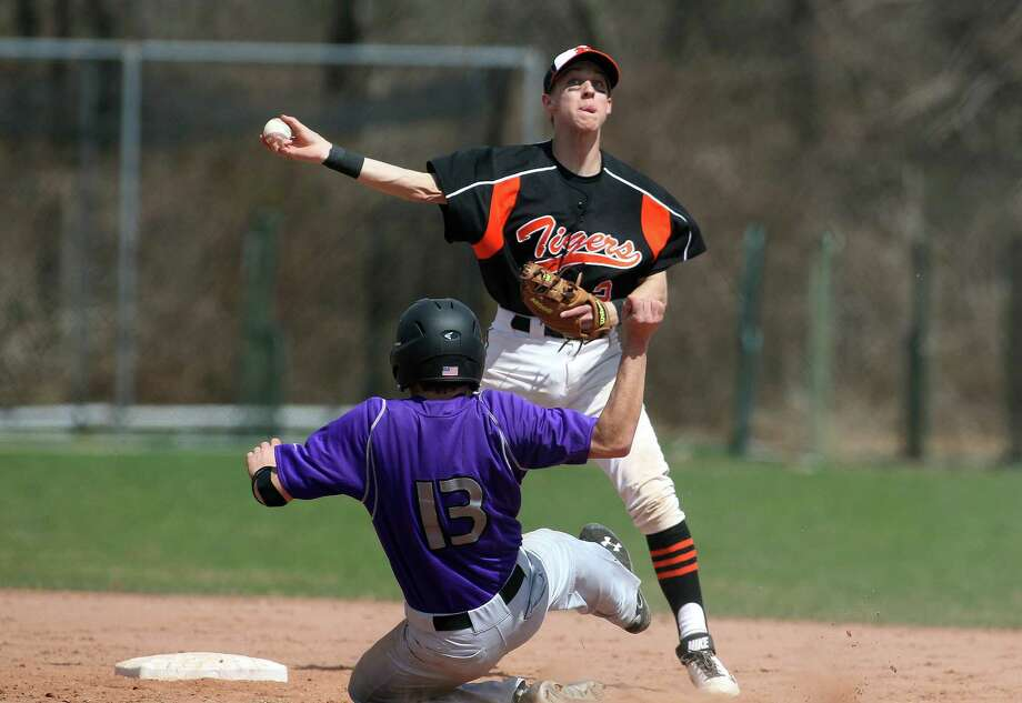 Ridgefield High School second baseman Liam Smith (# 2) forces out Westhill runner Mike Rossi (#13) on the front end of a double play ball during FCIAC baseball in Stamford, Conn. on Monday, April 14, 2014. Westhill won the tightly fought game, 5-4. Photo: J. Gregory Raymond / Stamford Advocate Freelance;  © J. Gregory Raymond