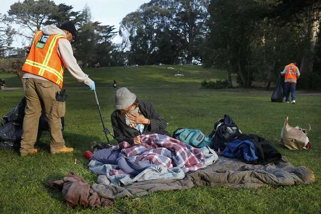 Paul Sunga a worker with San Francisco Park and Recreation Service  picks up trash as Mason Moody wakes up the morning after a 420 celebration on Hippie Hill in Golden Gate Park,  Monday April 21, 2014, in San Francisco, Calif. Photo: Lacy Atkins, SFC