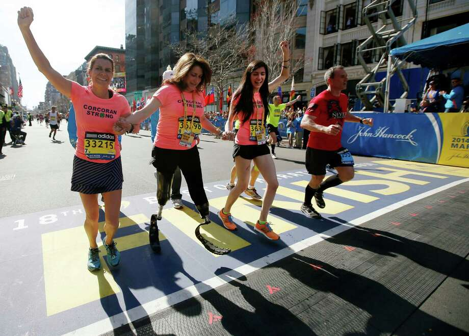 Double amputee Celeste Corcoran, center, a victim of last year's bombings, reaches the finish line of the 118th Boston Marathon, Monday, April 21, 2014, in Boston, with the aid her sister Carmen Acabbo, left, and daughter Sydney, right, who was also wounded last year. (AP Photo/Elise Amendola) ORG XMIT: BX231 Photo: Elise Amendola / AP