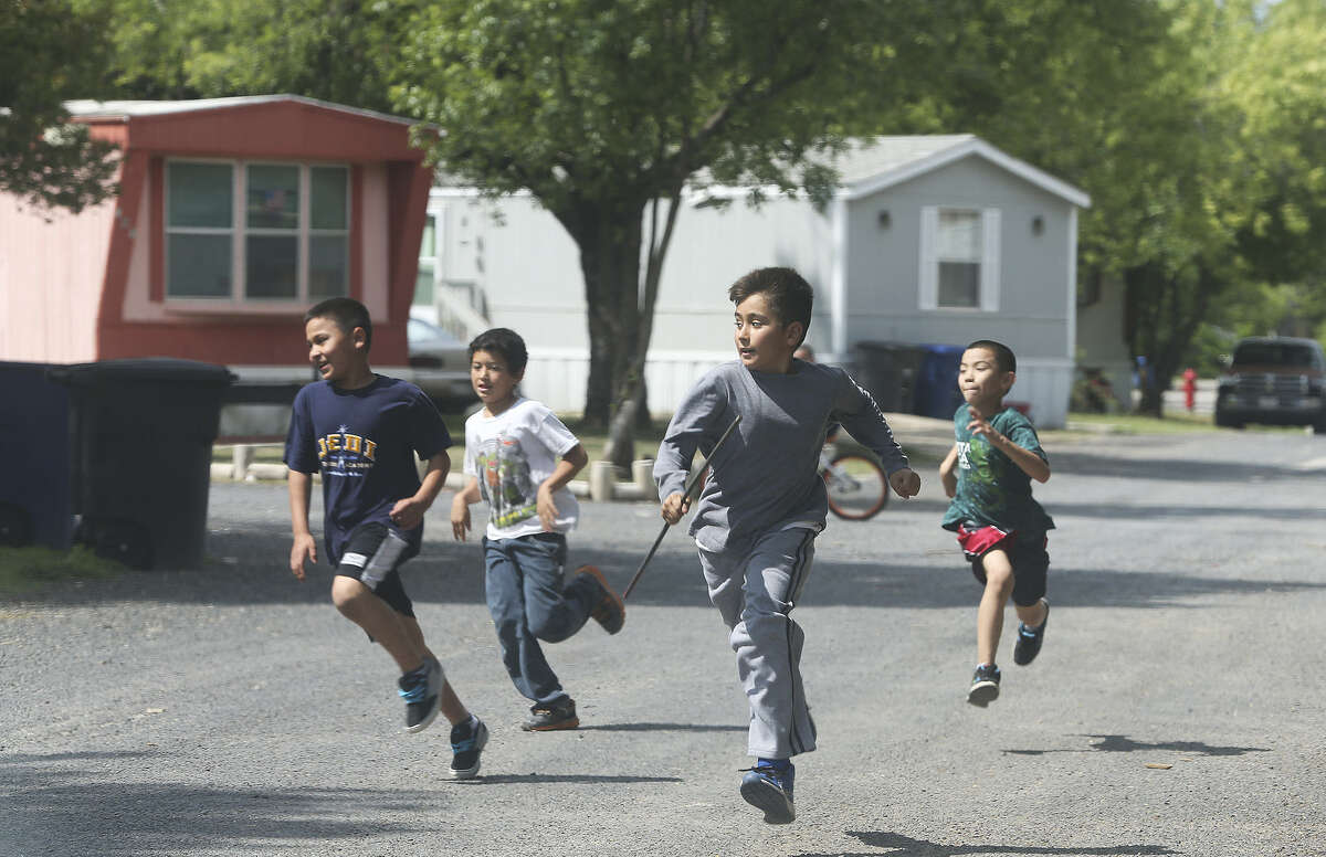 Boys play a chase game after school in the Mission Trail Mobile Home Park on April 18, 2014.