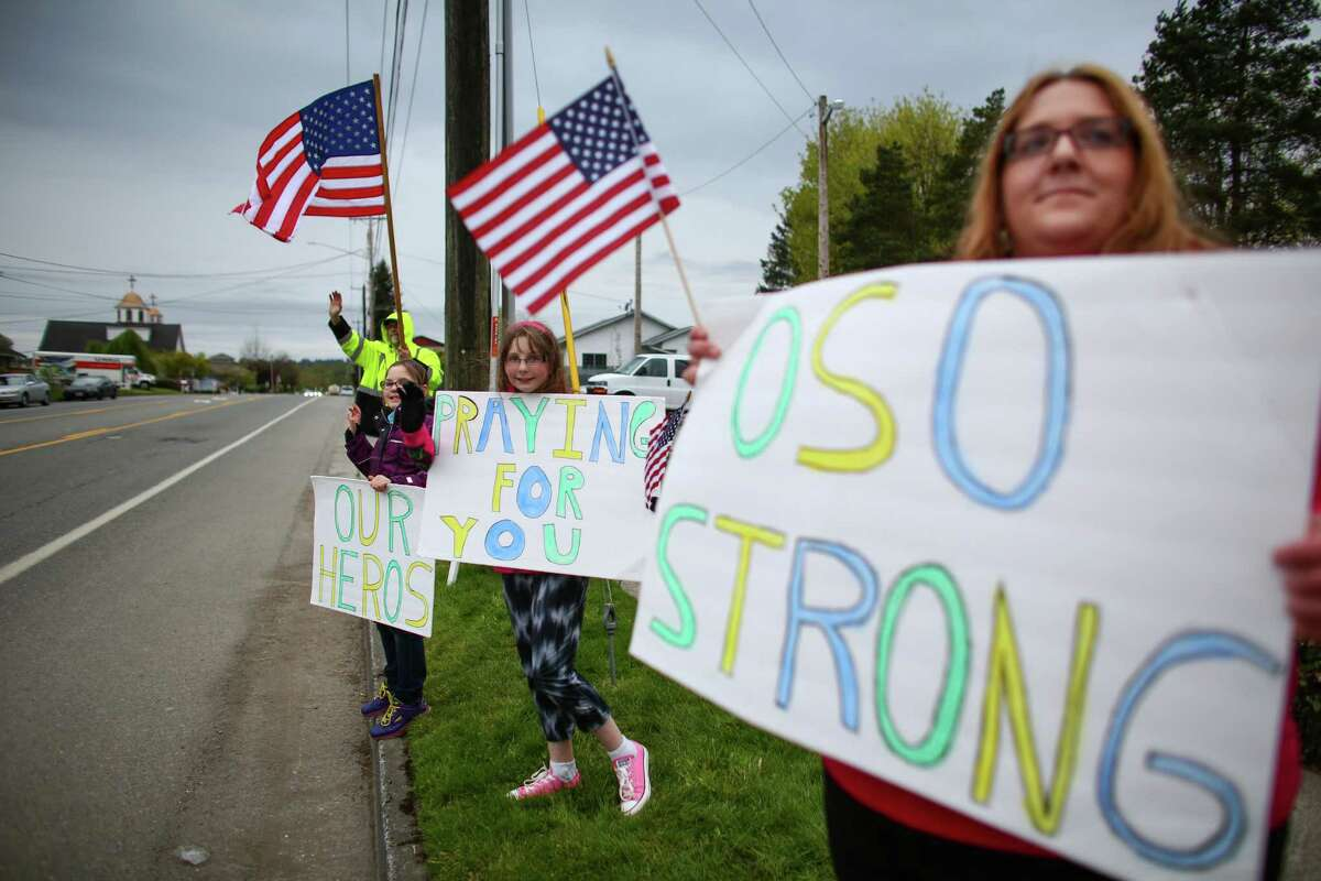 Jennifer Jaap, right, holds a sign along with Leah Powers, 11, left, and Jessica Tucker, 10, as rescue workers get off their shift near the Oso mudslide on Monday, April 21, 2014. Some in a group gathered waving signs of support said they come out each night to thank the rescue crews.