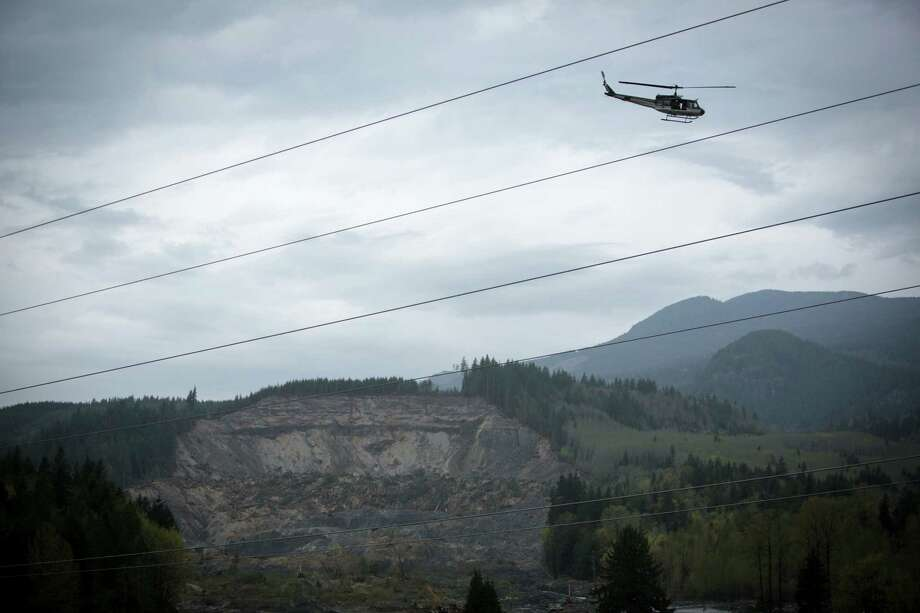 A helicopter flies over the scene of the Oso mudslide on Monday, April 21, 2014. The 22nd is the one month anniversary of the disaster that killed a confirmed 41 people. Two are still on the missing person list. Photo: JOSHUA TRUJILLO, SEATTLEPI.COM / SEATTLEPI.COM