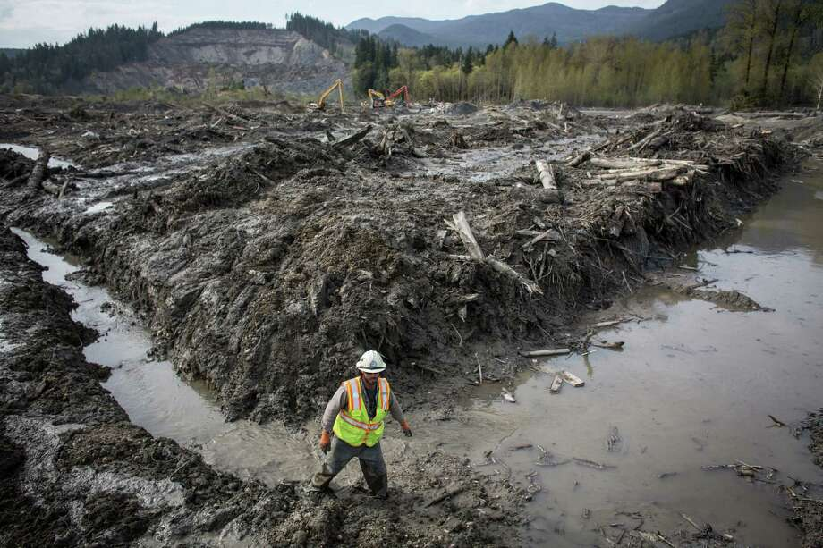 Ben Woodward slogs through thick mud at the scene of the Oso mudslide. Woodward, who usually helps manage wildfires, has adapted his skills to working the debris field in Oso. Photo: JOSHUA TRUJILLO, SEATTLEPI.COM / SEATTLEPI.COM