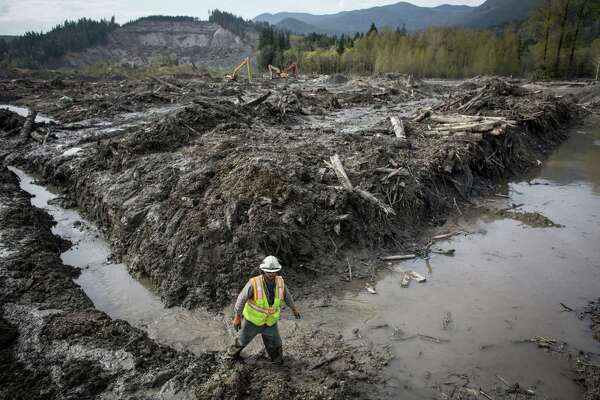 Ben Woodward slogs through thick mud at the scene of the Oso mudslide on Monday, April 21, 2014. The 22nd is the one month anniversary of the disaster that killed a confirmed 41 people. Two are still on the missing person list. Photographed on Monday, April 21, 2014.