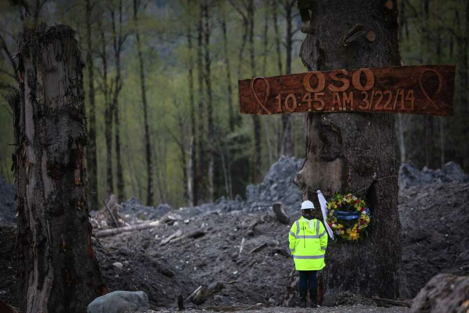A person pauses at a memorial commemorating the moment of the Oso mudslide. The wooden memorial was 