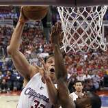 Los Angeles Clippers forward Blake Griffin, left, shoots over Golden State Warriors forward Harrison Barnes during the second half in Game 2 of an opening-round NBA basketball playoff series in Los Angeles, Monday, April 21, 2014. (AP Photo/Chris Carlson)