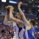 Los Angeles Clippers forward Blake Griffin, left, shoots around Golden State Warriors forward David Lee during the first half in Game 2 of an opening-round NBA basketball playoff series in Los Angeles, Monday, April 21, 2014. (AP Photo/Chris Carlson)