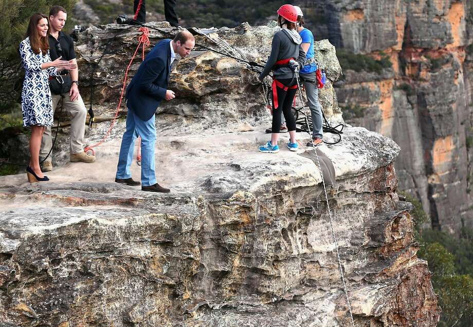 Britain's Prince William, third left, looks over the cliff edge as he and his wife Kate, the Duchess of Cambridge, left, observe abseiling and team building exercises at Narrow Neck Lookout near Katoomba, Australia, Thursday, April 17. The Duke and Duchess of Cambridge are on a three-week tour of Australia and New Zealand, the first official trip overseas with their son, Prince George of Cambridge. Photo: Ryan Pierse, Associated Press