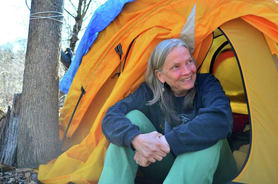 Nina Miller sits in the opening of her tent that she has slept in for more than 170 nights. Photo: Megan Spicer / Darien News