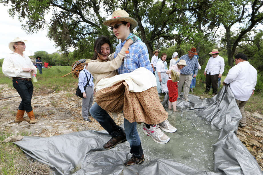 "Maxwell Kimball, 16, carries Gabriella Herrera, 17, across an ""icy river"", simulating the ""Sweetwater Crossing"" where three 18-year-old boys carried nearly every member of their handcart company across a snowbound stream, during the San Antonio West Stake Pioneer Trek at the McGimsey Boy Scout Park on Friday, April 18, 2014.  Approximately 170 Mormon youths from the stake participated in the Trek, camping overnight and experiencing what it was like when the Mormons migrated to Salt Lake City in Utah from the midwest in the mid-1800's. MARVIN PFEIFFER/ mpfeiffer@express-news.net Photo: MARVIN PFEIFFER, Marvin Pfeiffer/ EN Communities / Express-News 2014"