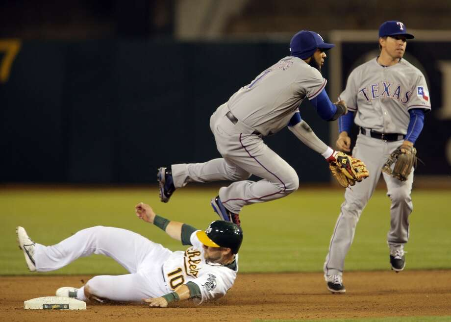 Daric Barton caught in a double play in the fourth inning, as Elvis Andrus throws to get Eric Sogard at first. The Oakland Athletics played the Texas Rangers at O.co Coliseum in Oakland, Calif., on Monday, April 21, 2014. Photo: Carlos Avila Gonzalez, The Chronicle