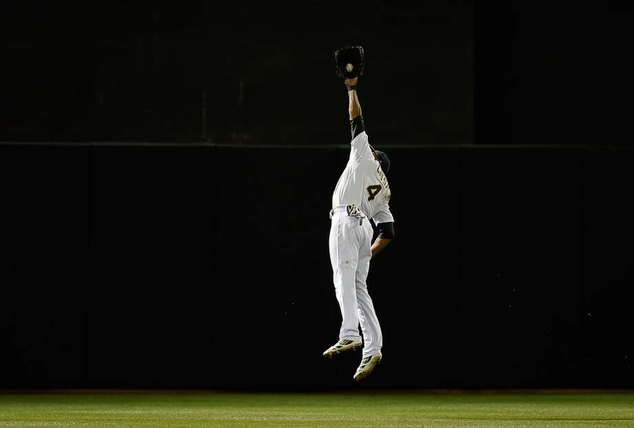 Coco Crisp #4 of the Oakland Athletics leaps to take a hit away from Elvis Andrus of the Texas Rangers in the top of the seventh inning at O.co Coliseum on April 21, 2014 in Oakland, California. Photo: Thearon W. Henderson, Getty Images