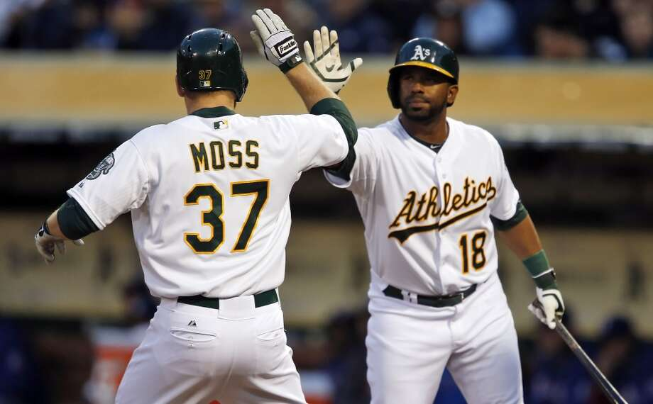 Alberto Callaspo, right, high fives Brandon Moss, left, after Moss hit a homerun in the bottom of the second inning. The Oakland Athletics played the Texas Rangers at O.co Coliseum in Oakland, Calif., on Monday, April 21, 2014. Photo: Carlos Avila Gonzalez, The Chronicle