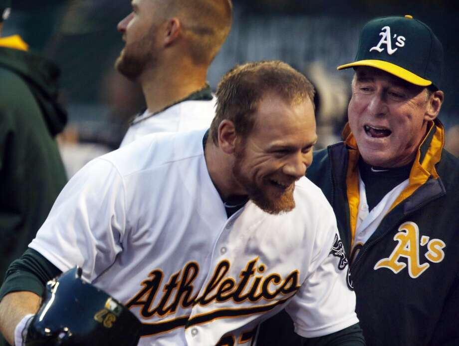 Brandon Moss is congratulated by Bob Melvin after hitting a solo homerun in the bottom of the second inning. The Oakland Athletics played the Texas Rangers at O.co Coliseum in Oakland, Calif., on Monday, April 21, 2014. Photo: Carlos Avila Gonzalez, The Chronicle