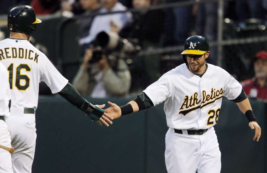 Josh Reddick, left, high fives Eric Sogard, right, after they both scored on a Coco Crisp single in the bottom of the second inning. The Oakland Athletics played the Texas Rangers at O.co Coliseum in Oakland, Calif., on Monday, April 21, 2014. Photo: Carlos Avila Gonzalez, The Chronicle