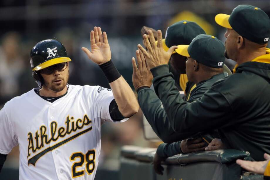 Eric Sogard returns to the dugout to high fives from teammates after scoring in the second inning. The Oakland Athletics played the Texas Rangers at O.co Coliseum in Oakland, Calif., on Monday, April 21, 2014. Photo: Carlos Avila Gonzalez, The Chronicle