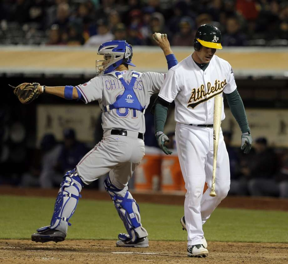 John Jaso, right, flips his bat after striking out in the ninth inning. The Oakland Athletics played the Texas Rangers at O.co Coliseum in Oakland, Calif., on Monday, April 21, 2014, losing 3-4. Photo: Carlos Avila Gonzalez, The Chronicle