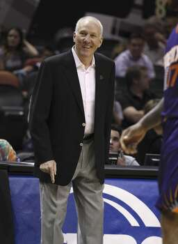 Spurs coach Gregg Popovich cracks a smile during the game against the Phoenix Suns in the first half at the AT&T Center on Friday, Apr. 11, 2014. (Kin Man Hui/San Antonio Express-News) Photo: Kin Man Hui, San Antonio Express-News