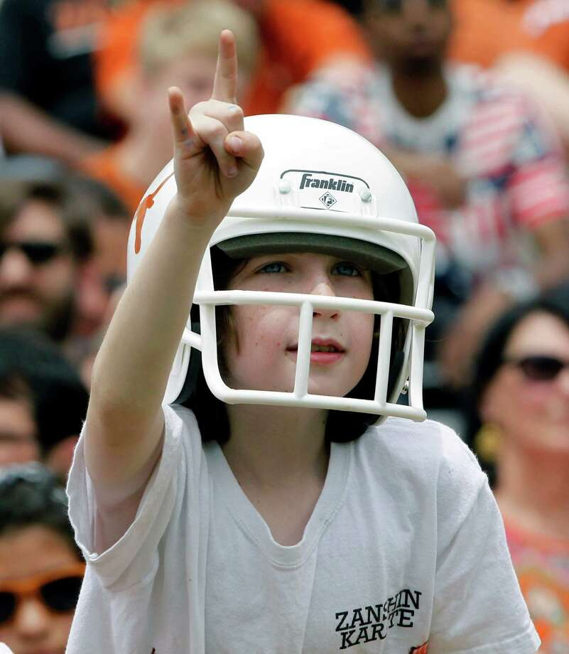 "A young Texas fan gives the ""Hook 'em Horns"" sign during the first half of the Orange and White spring NCAA college football game on Saturday, April 19, 2014, in Austin, Texas. (AP Photo/Michael Thomas) Photo: Michael Thomas, Associated Press / FR65778 AP"