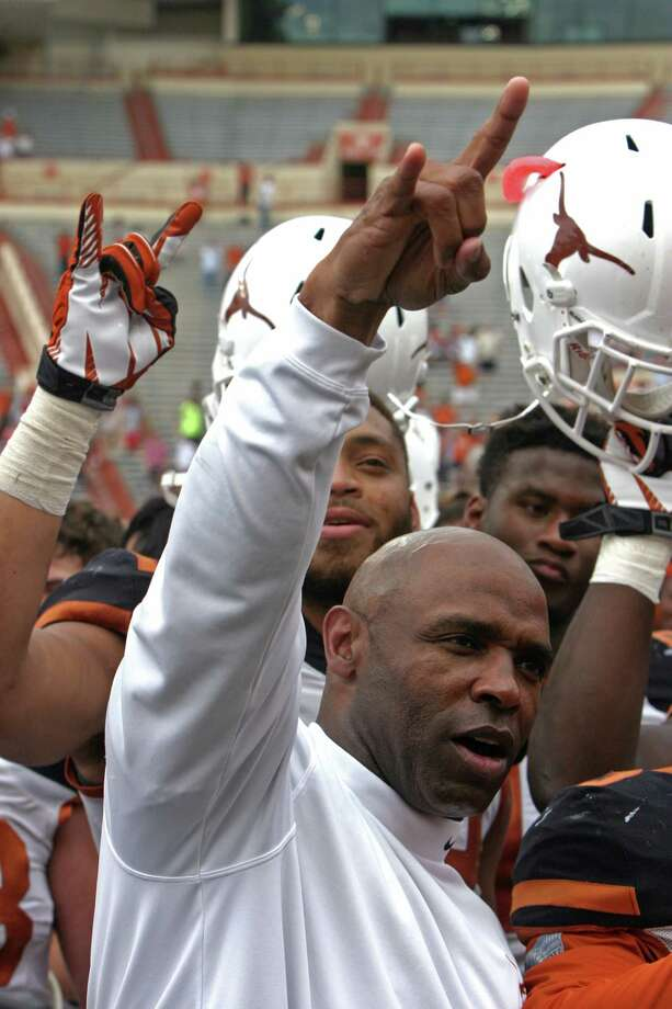 "Texas coach Charlie Strong gives the ""hook 'em horns"" sign while his players raise their helmets after the Orange and White spring NCAA college football game, Saturday, April 19, 2014, in Austin, Texas.  (AP Photo/Michael Thomas) Photo: Michael Thomas, Associated Press / FR65778 AP"