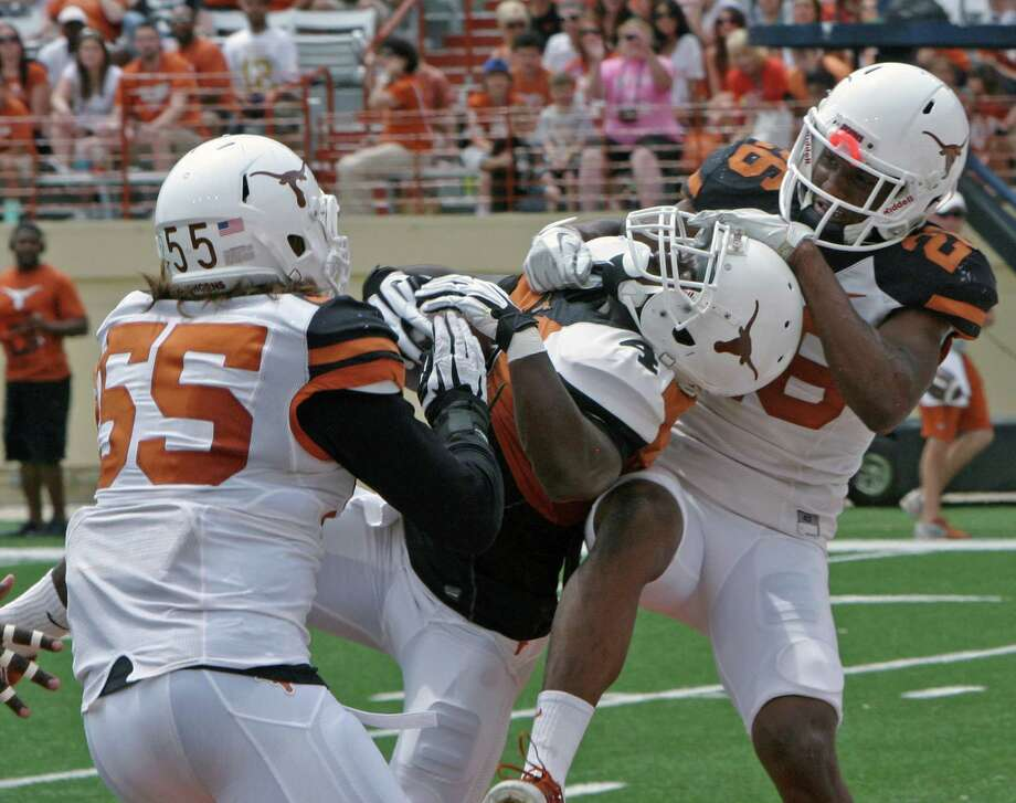 Texas running back Daje Johnson (4) pulls down a pass for a touchdown against Dalton Santos (55)  and Adrian Colbert (26) during the first half of the Orange and White spring NCAA college football game, Saturday, April 19, 2014, in Austin, Texas. (AP Photo/Michael Thomas) Photo: Michael Thomas, Associated Press / FR65778 AP