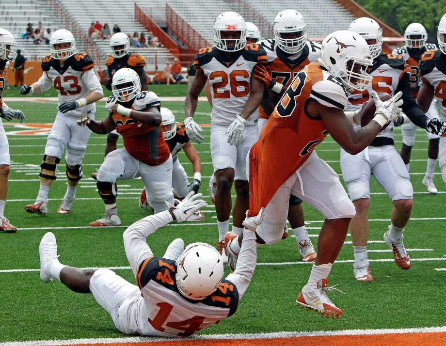 Texas running back Malcolm Brown (28) rushes for a touchdown against Chevoski Collins (14) during the first half of the Orange and White spring NCAA college football game on Saturday, April 19, 2014, in Austin, Texas. (AP Photo/Michael Thomas) Photo: Michael Thomas, Associated Press / FR65778 AP