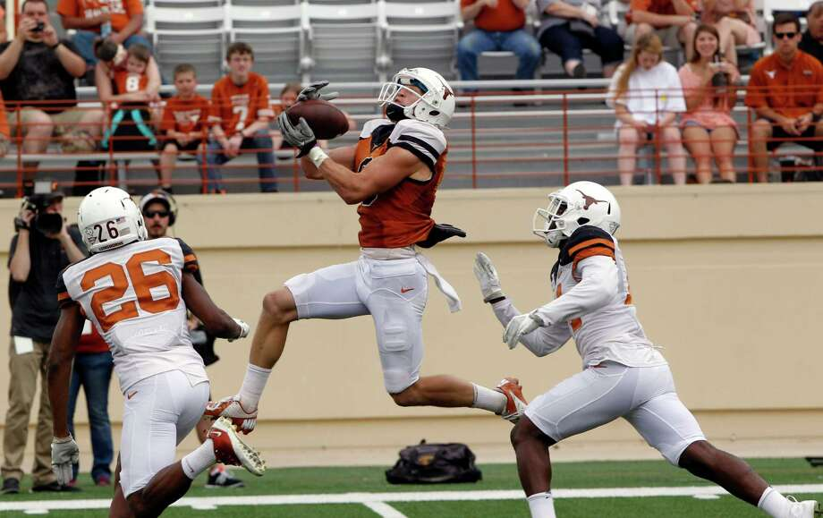 Texas receiver Jaxson Shipley, center, catches a touchdown pass against Adrian Colbert (26) and Chevoski Collins during the second half of the Orange and White spring NCAA college football game on Saturday, April 19, 2014, in Austin, Texas. (AP Photo/Michael Thomas) Photo: Michael Thomas, Associated Press / FR65778 AP