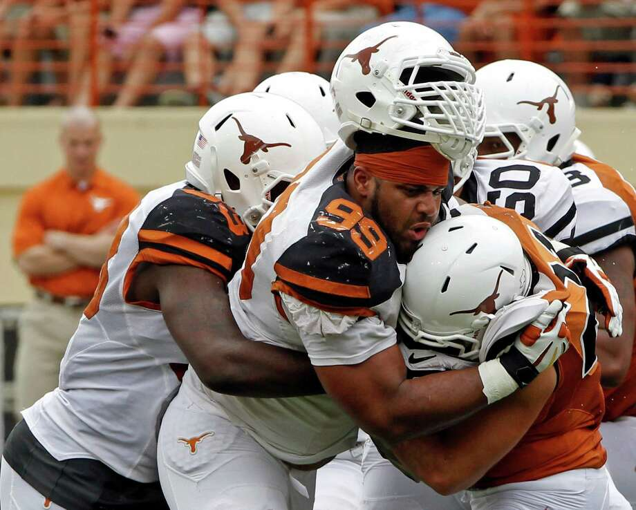Texas defensive lineman Desmond Jackson (99) tackles Eddie Aboussie (21) with help from Steve Edmond (33) during the first half of the Orange and White spring NCAA college football game on Saturday, April 19, 2014, in Austin, Texas. (AP Photo/Michael Thomas) Photo: Michael Thomas, Associated Press / FR65778 AP
