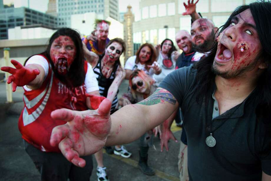 """Houston Zombie Walk members will take part as walkers, survivors and promoters of their charity in """"The Walking Dead Escape"""" Saturday at Reliant Stadium. We asked for a sneak peek at their best undead moves: Daniella Hernandez, left foreground, and German Alexander reach for fresh flesh. Special effects makeup donated by Halloween Express. Photo: Mayra Beltran, Staff / © 2014 Houston Chronicle"""