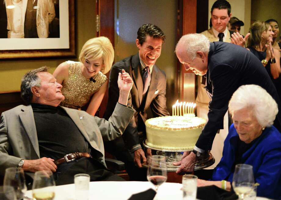 President George H.W. Bush is serenaded by Marilyn Monroe impersonator Mary Milius at his pre-birthday bash as Milton Townsend, left, and Jackson Hicks bring a large carrot cake to the table shared by Barbara Bush. Photo: Al Torres Photography / AL TORRES         PHOTOGRAPHY