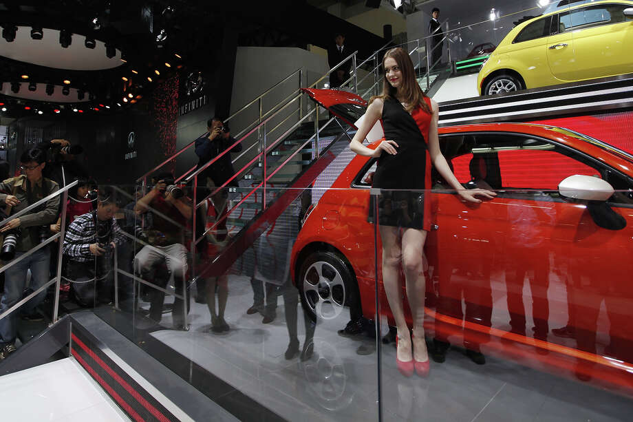 "A model (C) poses by a Fiat car on display at the China International Exhibition Center venue during the ""Auto China 2014,"" the Beijing International Automotive Exhibition, in Beijing on April 20, 2014. Photo: AFP, Wire Images / AFP"