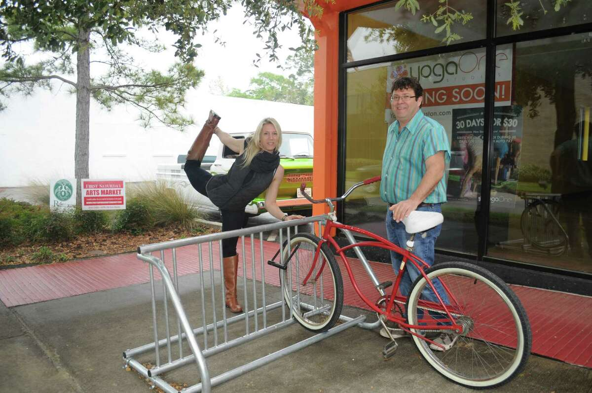 YogaOne owner Dana Sweet,left, and Mitch Cohen stand by the Bike Rack in the Heights.