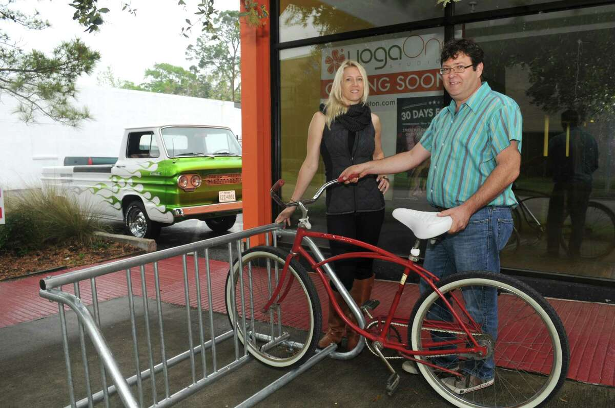 YogaOne owner Dana Sweet, left, and Mitch Cohen stand by one of the racks Cohen installed in the Heights to serve local cyclists.