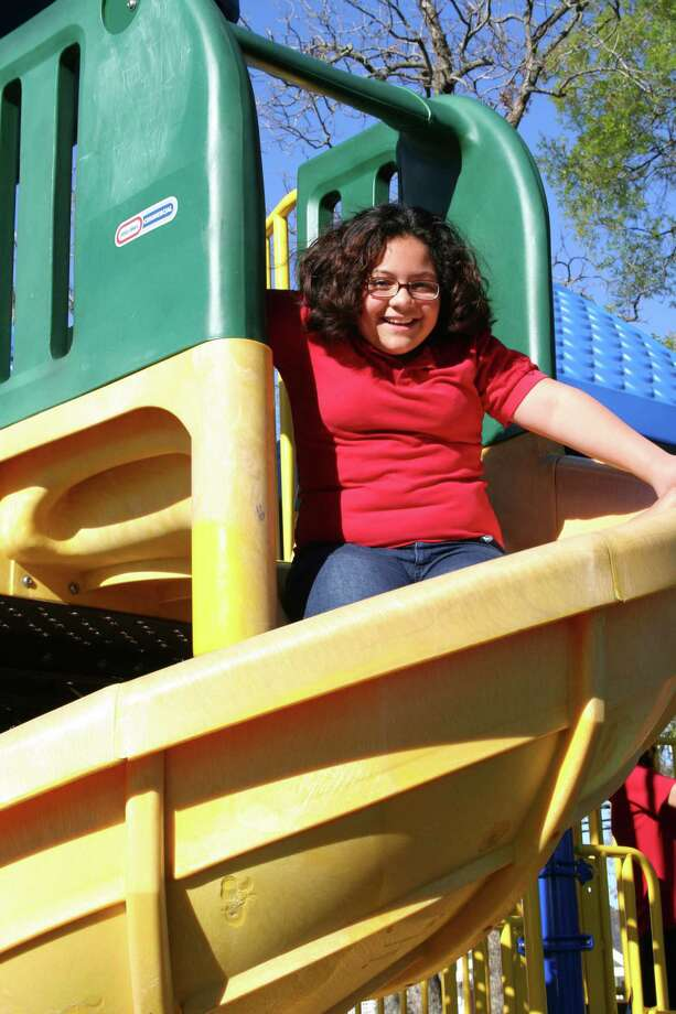 Emily Ybanez's favorite part of the new playground equipment in the Treasure Forest Elementary School is the slide. Photo: Tom Behrens