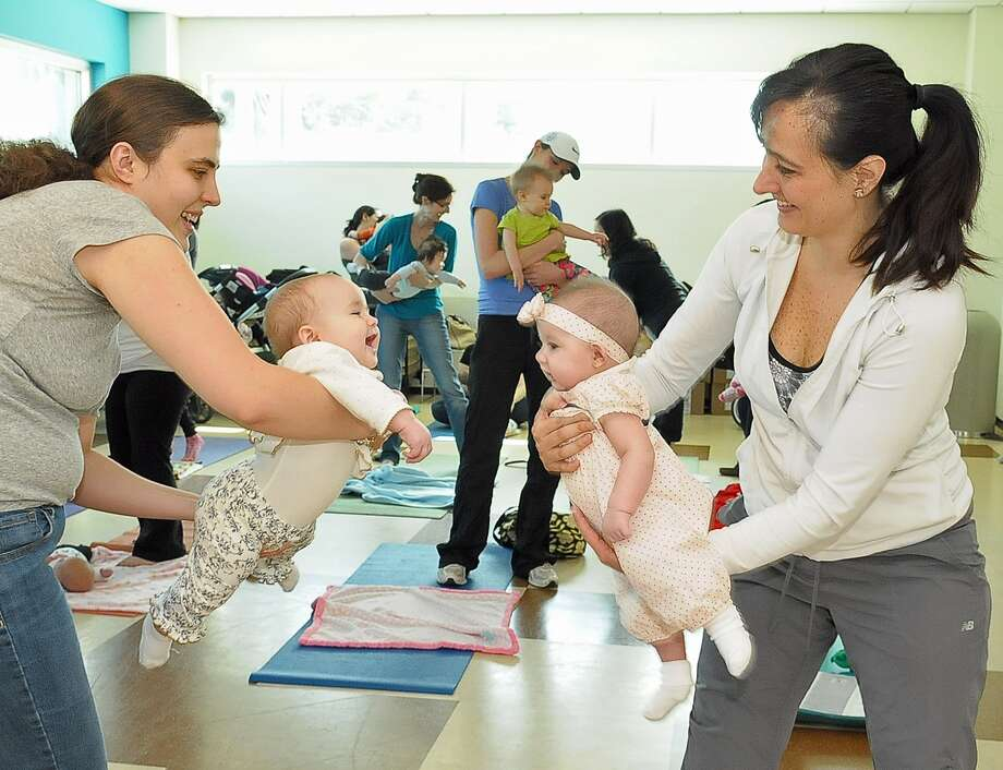 "Amanda Braniff, left, and her 7-month-old daughter Eva  work out with Elina Rock and her 4-month-old daughter Sara during a ""Baby Yoga"" class at Kendall Neighborhood Library. Programs offered through the library and community center focus on a wide range of ages and interests. Photo: Â Tony Bullard 2014, Freelance Photographer / © Tony Bullard & the Houston Chronicle"