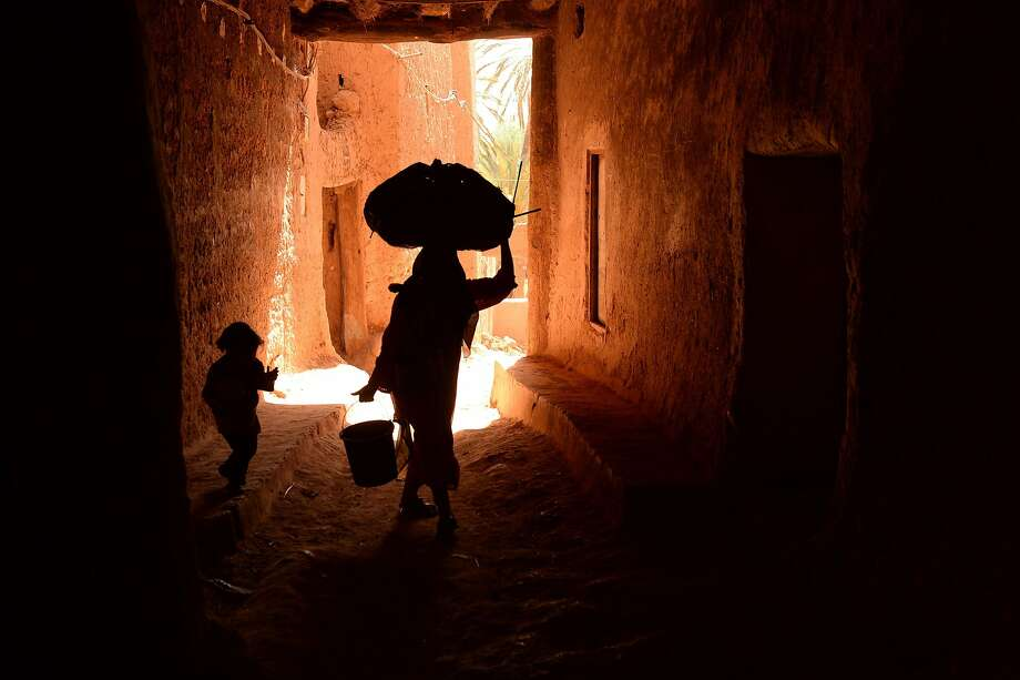 With a bundle on her head and a bucket in her hand, a woman makes her way with her daughter through an alley in the old part of Tinghir, Morocco. Photo: Fadel Senna, AFP/Getty Images