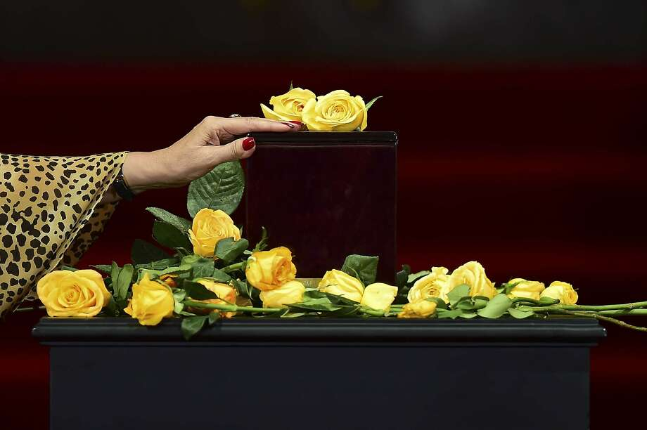 Yellow roses for the author:A woman touches the urn containing his ashes of Colombian novelist Gabriel Garcia Marquez, 