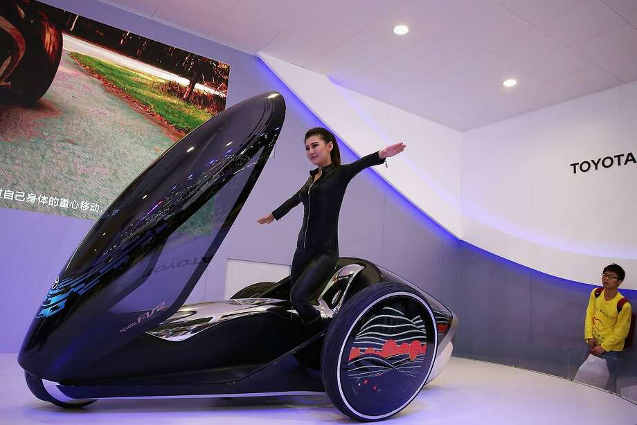 More fun to tip than a Smart Car:A model does calisthenics on the Toyota FV2 concept car during the Beijing International Automotive Exhibition. Photo: Feng Li, Getty Images