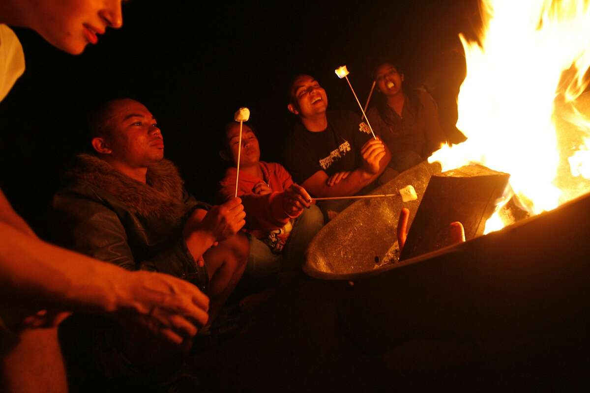 Brendan Espinoza of Pacifica (l to r), Bryan Ramirez of So. San Francisco, Louise Jabagat of San Francisco, Randy Sullins of So. San Francisco and an unidentified young lady enjoyed the day's good weather in San Francisco, Calif. into the night on Ocean Beach in San Francisco, Calif. as they roasted hot dogs and marshmallows at a fire on the beach on Thursday August 28, 2008.