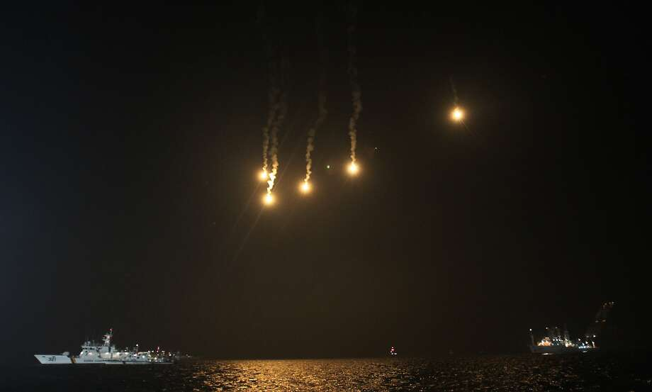 Flares illuminate the sky as a South Korean Coast Guard ship sails to look for people believed to have been trapped in the sunken ferry Sewol in the water off the southern coast near Jindo, south of Seoul, South Korea, Tuesday, April 22, 2014. One by one, coast guard officers carried the newly arrived bodies covered in white sheets from a boat to a tent on the dock of this island, the first step in identifying a sharply rising number of corpses from the South Korean ferry that sank nearly a week ago. (AP Photo/Ahn Young-joon) Photo: Ahn Young-joon, Associated Press