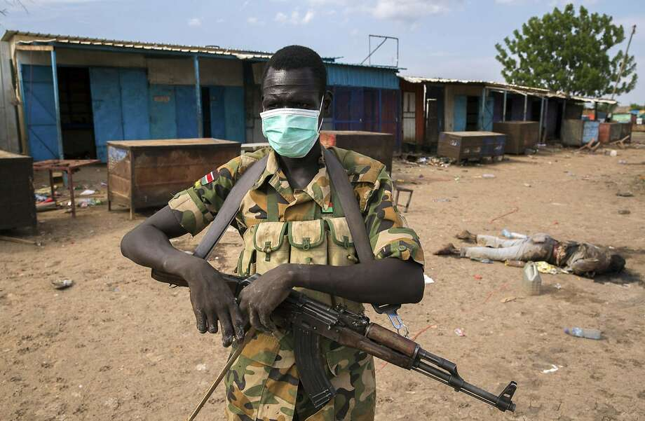 A rebel fighter wears a mask near a body in front of a mosque where people were massacred at Bentiu in Unity state. Photo: Stringer, Reuters