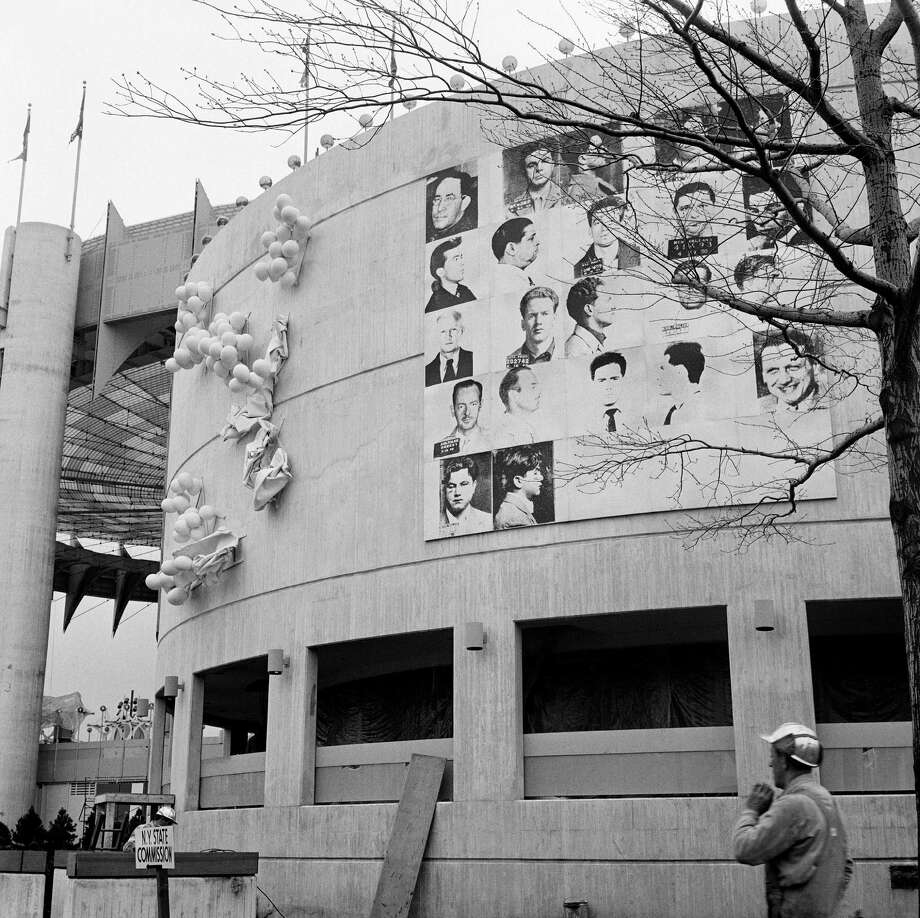 "This April 1964 photo provided by The Andy Warhol Foundation for the Visual Arts, Inc. shows a 20x20 foot mural depicting mug shots of the NYPD's 13 most-wanted criminals by Andy Warhol, mounted on the curved facade of the New York State Pavilion at the 1964 New York World's Fair in the Queens borough of New York. The fair celebrated ""The World of Tomorrow,"" but Warhol may have been ahead of his time. His monumental piece commissioned specifically for the fair was deemed too edgy for the family-friendly event and painted over just before opening day. Now, 50 years later, the work is the focus of a museum exhibition being staged on the very fairgrounds where the pop-art provocateur was infamously censored. (AP Photo/The Andy Warhol Foundation for the Visual Arts, Inc./Artists Rights Society) ORG XMIT: NYR301 / The Andy Warhol Foundation for the Visual Arts, Inc./Artists Rig"