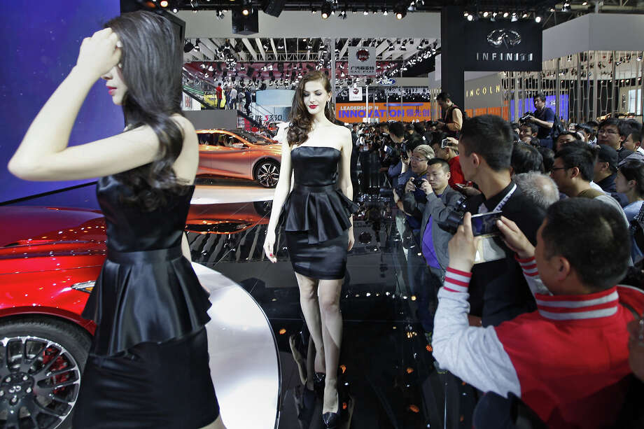 "Models pose by Infiniti cars on display at the ""Auto China 2014"" Beijing International Automotive Exhibition in Beijing on April 21, 2014.  Leading automakers have gathered in Beijing for the kickoff of China's biggest car show, but lackluster growth and environmental restrictions in the world's largest car market have thrown uncertainty into the mix. Photo: STR, Wire Images / AFP"