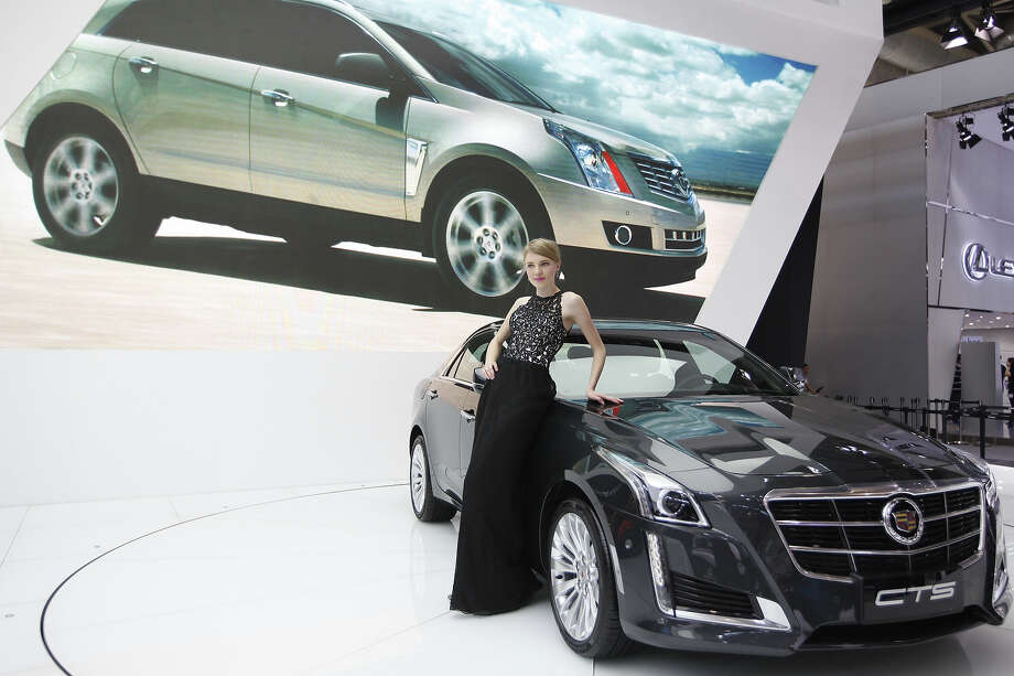 "A model poses by a Cadillac CTS car at the China International Exhibition Center new venue during the ""Auto China 2014"" Beijing International Automotive Exhibition in Beijing on April 21, 2014. Leading automakers are gathering in Beijing for the kickoff of China's biggest car show, but lackluster growth and environmental restrictions in the world's largest car market have thrown uncertainty into the mix. More than 1,100 vehicles are being showcased at the auto show, which opens to the public on April 21. Photo: AFP, Wire Images / AFP"