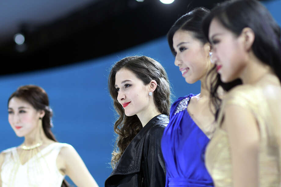 "Models pose for photos at the China International Exhibition Center during the ""Auto China 2014"" Beijing International Automotive Exhibition in Beijing on April 21, 2014.  Leading automakers have gathered in Beijing for the kickoff of China's biggest car show, but lackluster growth and environmental restrictions in the world's largest car market have thrown uncertainty into the mix. Photo: STR, Wire Images / AFP"