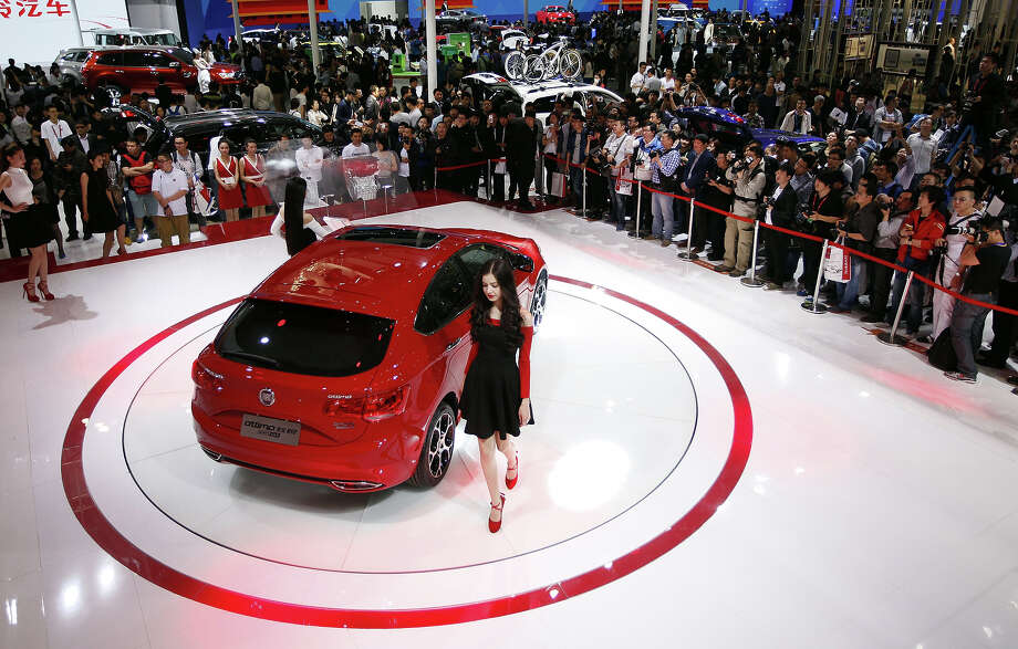 "Visitors gather to look at a GAC Fiat car on display at the ""Auto China 2014"" Beijing International Automotive Exhibition in Beijing on April 21, 2014.  Leading automakers have gathered in Beijing for the kickoff of China's biggest car show, but lackluster growth and environmental restrictions in the world's largest car market have thrown uncertainty into the mix. Photo: STR, Wire Images / AFP"