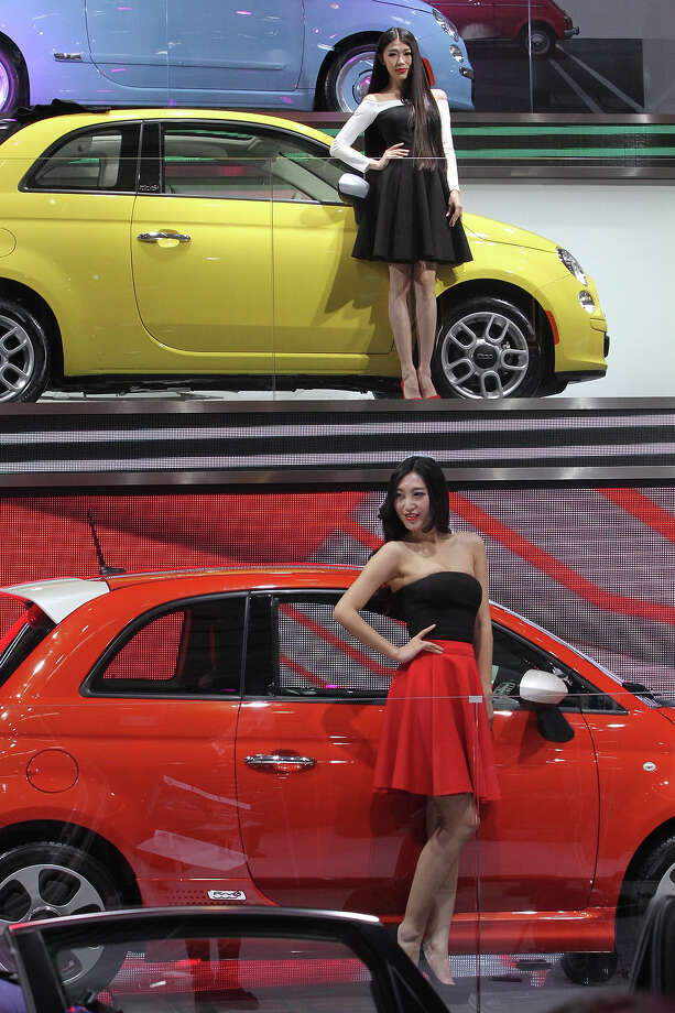 "Models pose by GAC Fiat cars in an exhibition hall at the China International Exhibition Center during the ""Auto China 2014"" Beijing International Automotive Exhibition in Beijing on April 20, 2014.  Leading automakers are gathering in Beijing for the kickoff of China's biggest car show, but lackluster growth and environmental restrictions in the world's largest car market have thrown uncertainty into the mix. More than 1,100 vehicles are being showcased at the auto show, which opens to the public on April 21. Photo: AFP, Wire Images / AFP"