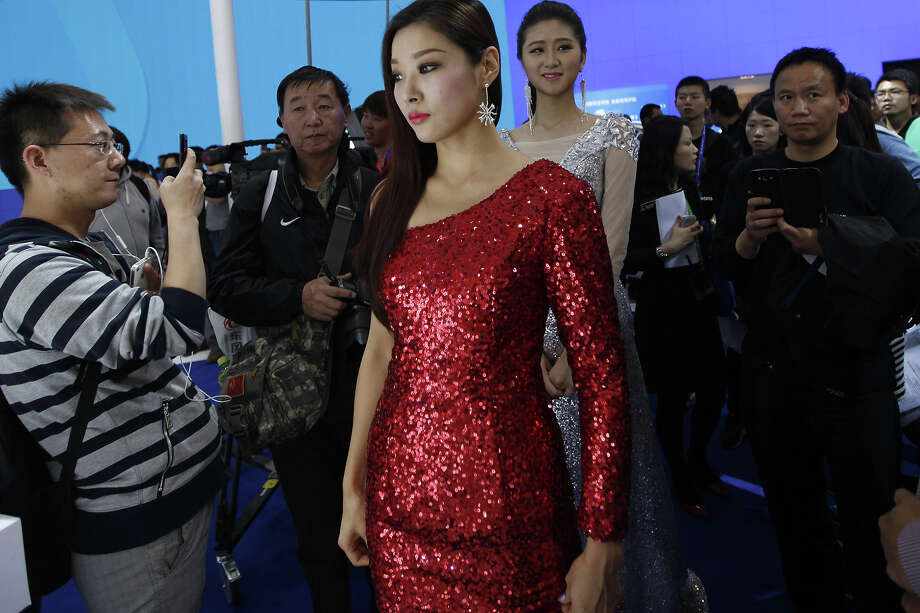 """Car models (C) wait to perform on stage at the China International Exhibition Center new venue during the """"Auto China 2014"""" Beijing International Automotive Exhibition in Beijing on April 21, 2014. Leading automakers are gathering in Beijing for the kickoff of China's biggest car show, but lackluster growth and environmental restrictions in the world's largest car market have thrown uncertainty into the mix. More than 1,100 vehicles are being showcased at the auto show, which opens to the public on April 21. Photo: AFP, Wire Images / AFP"""