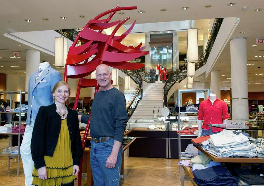 Kristin Tichy, Visual Director at Richards, left, and artist Denis Folz, right, pose for a photo with one of Folz' pieces inside the Greenwich store on Tuesday, April 22, 2014. Photo: Lindsay Perry / Stamford Advocate